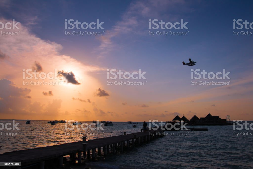 Clubmed Maldives front beach view before sunset with seaplane flying through the scene stock photo