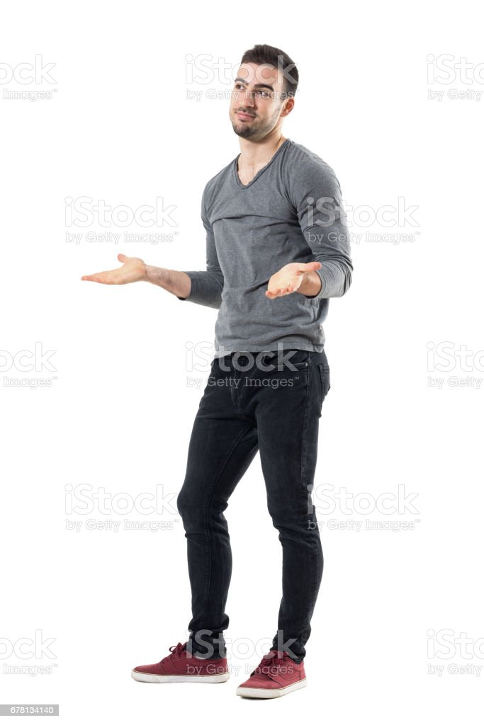 Clueless confused young man shrugging shoulders looking away stock photo