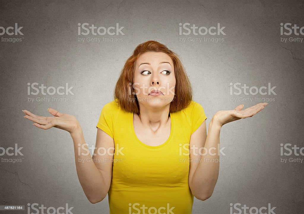 Clueless woman with arms out shrugs shoulders stock photo