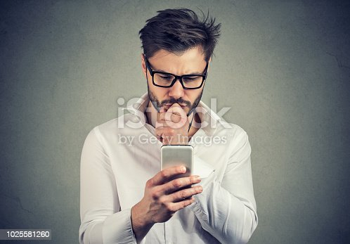 istock Clueless young man having troubles with his smartphone 1025581260