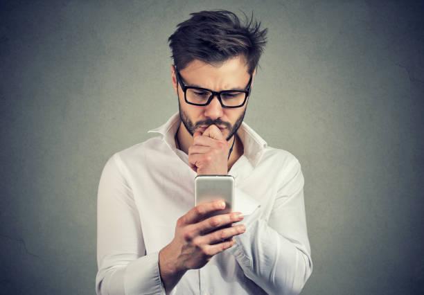 Ahnungslosen jungen Mann Probleme mit seinem smartphone – Foto
