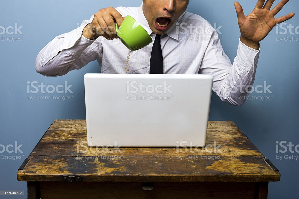 Clumsy businessman spilling coffee on his laptop computer stock photo