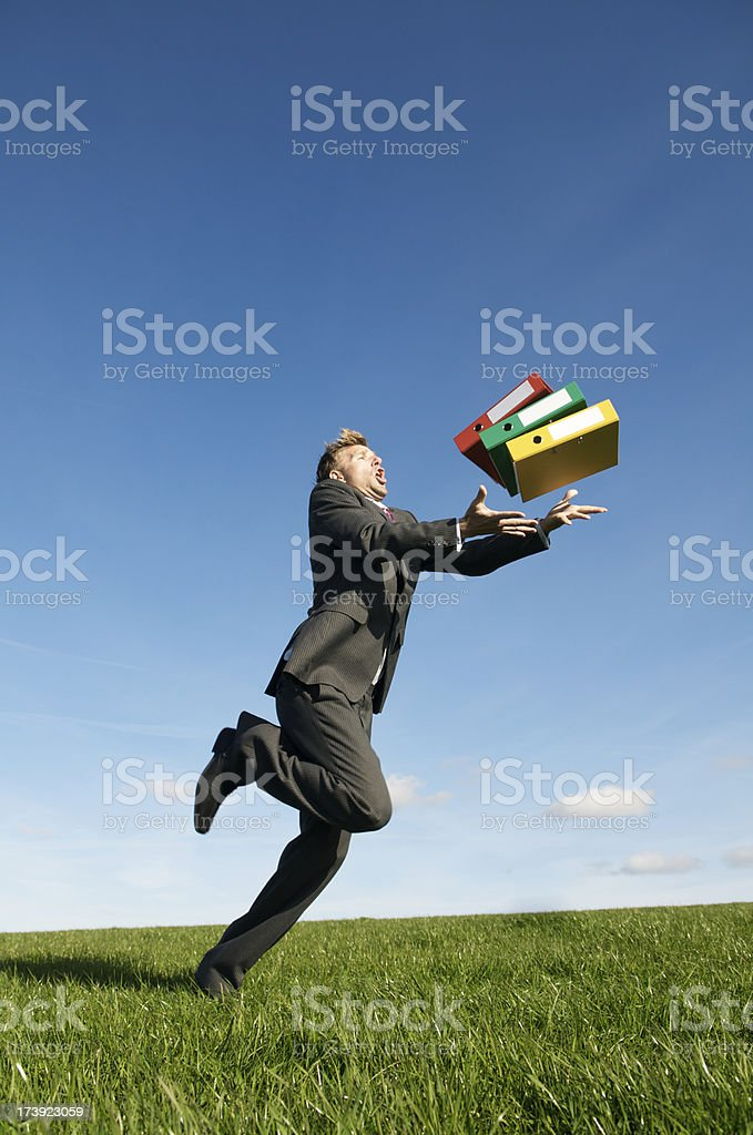 Clumsy Businessman Tripping and Dropping His Files in Meadow royalty-free stock photo