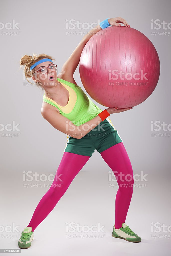Clumsy funny girl wearing glasses holding big fitness ball royalty-free stock photo