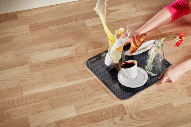Clumsy person Woman falls / stumbles with a full serving tray on a wooden floor. Everything on the ground flies up in the air slow motion stock pictures, royalty-free photos & images
