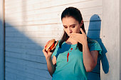 istock Clumsy Woman Staining Her Shirt with Ketchup Sauce 1140336345