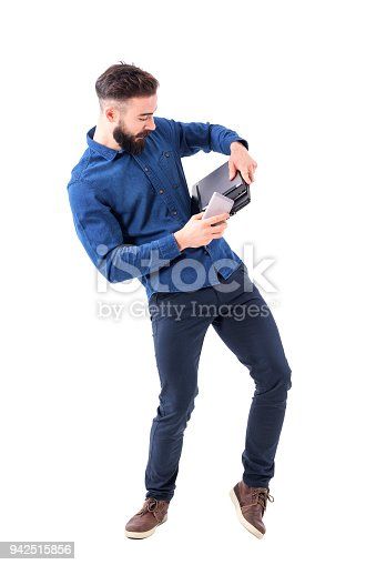 istock Clumsy young bearded businessman holding laptop, tablet and cell phone from falling down 942515856