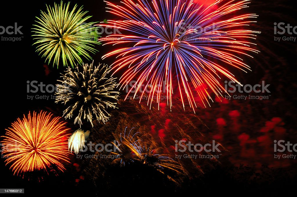 Cluster of colorful fireworks against dark sky stock photo