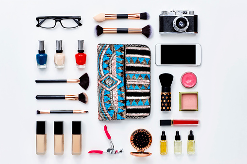 Directly above flat lay shot of clutch bag surrounded with beauty products. Various personal accessories are arranged with technologies. They are placed on white background. Knolling Concept.