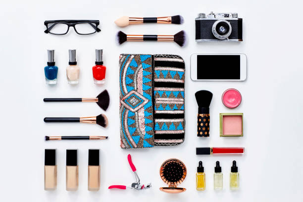 Clutch bag surrounded with beauty products and technologies Directly above flat lay shot of clutch bag surrounded with beauty products. Various personal accessories are arranged with technologies. They are placed on white background. Knolling Concept. knolling concept stock pictures, royalty-free photos & images