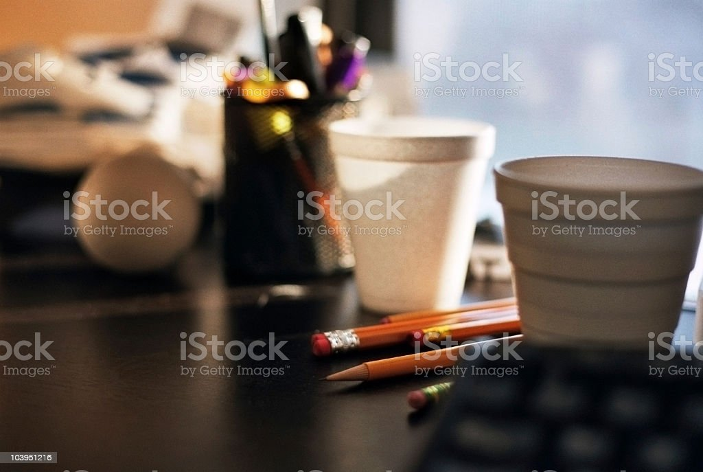 Cluttered Desktop Covered With Styrofoam Cups and Pencils stock photo