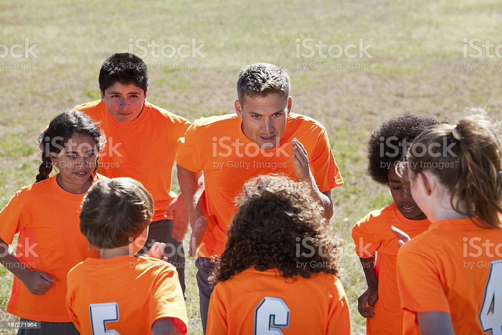 Coach with team of children in sports uniform, strategizing.