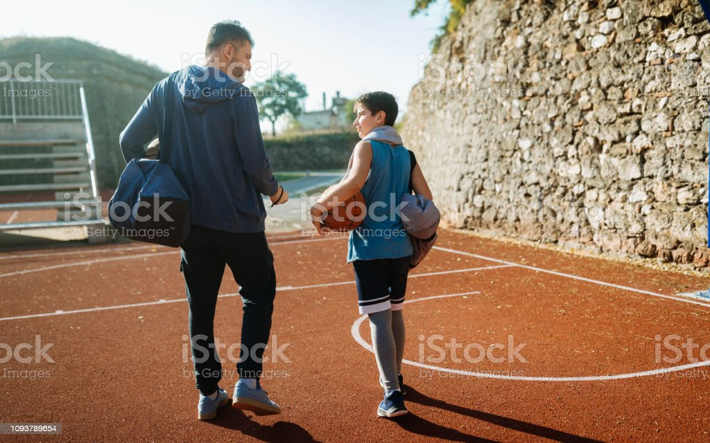Photo of coach with his young basketball player talking after training