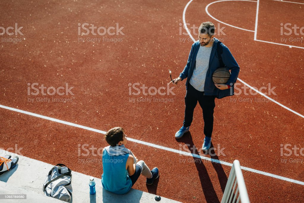 Photo of coach with his young basketball player talking a break from...