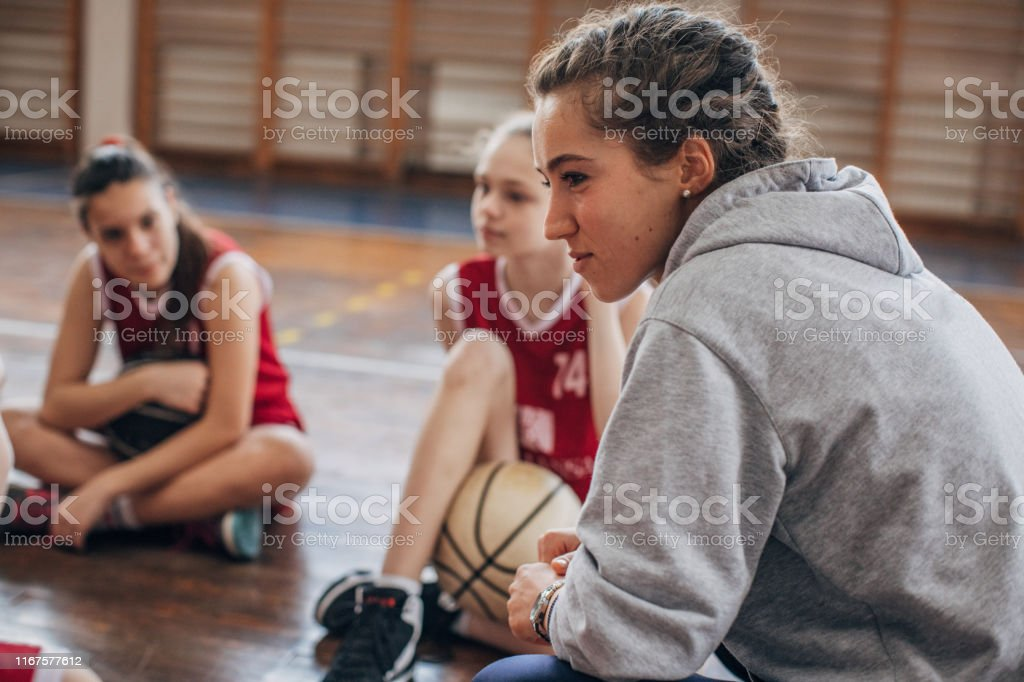 Female coach standing with basketball team on basketball court
