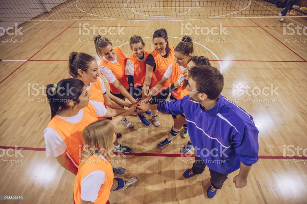 Group of women and coach, holding hands before volleyball game.