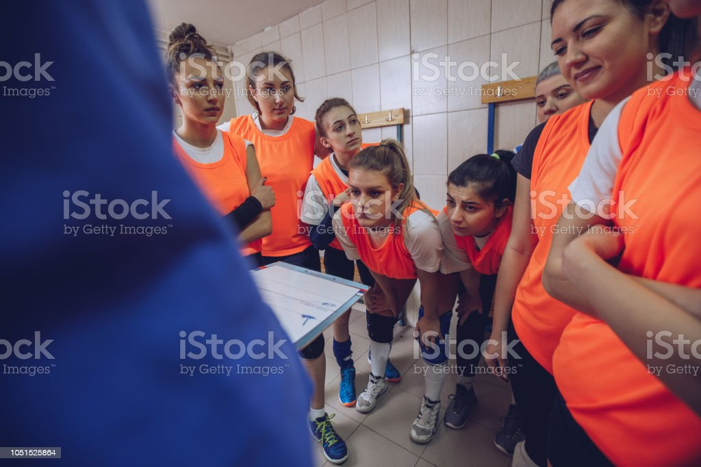 Group of women and coach, talking strategy in locker room before...