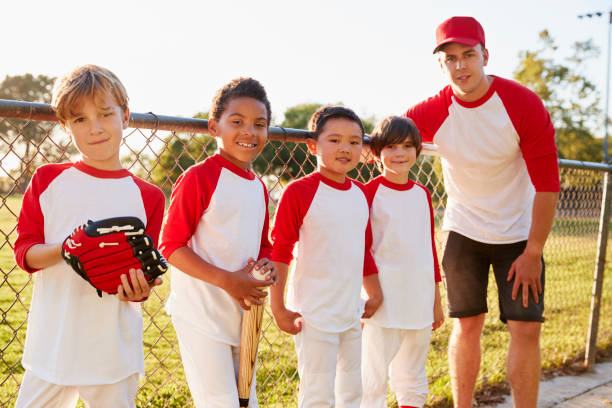 Coach and young boys in a baseball team looking to camera Coach and young boys in a baseball team looking to camera baseball sport stock pictures, royalty-free photos & images