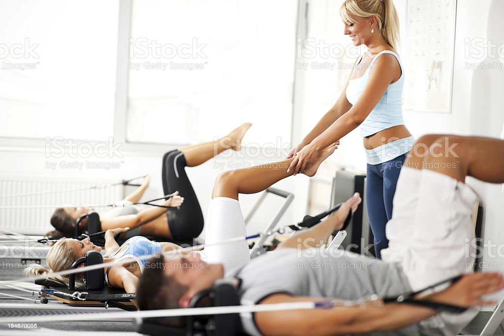 Coach assisiting the girl exercising on Pilates machine. stock photo