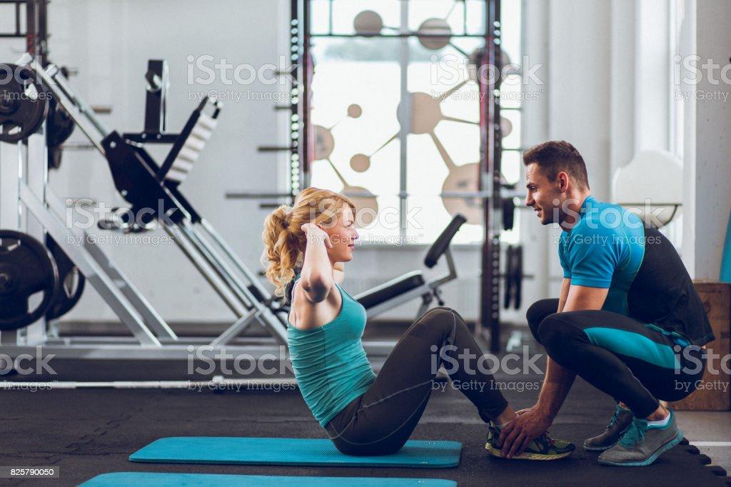 ジムで腹筋を行う若い女性の支援コーチ ストックフォト