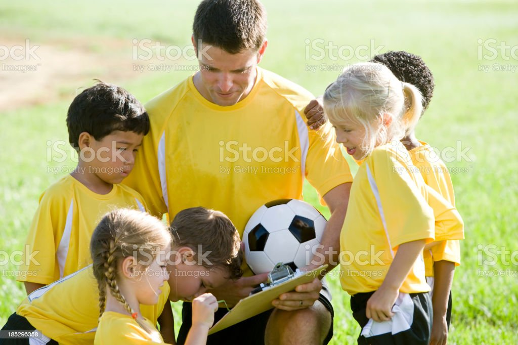 Coach coaching diverse young team of soccer players stock photo