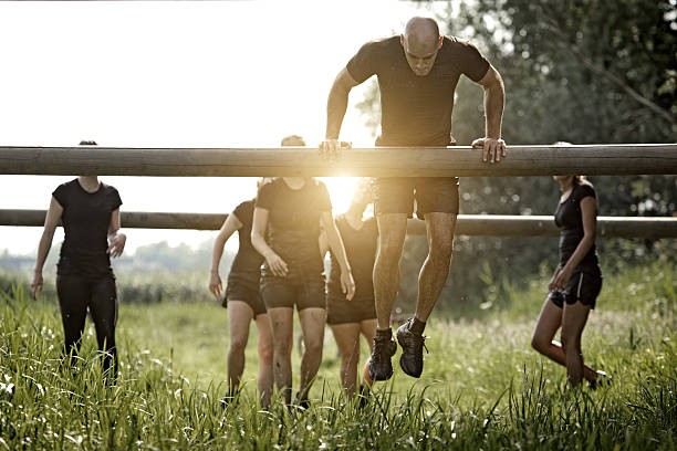 coach demonstrating to group of women how to cross obstacle coach demonstrating to group of women how to cross wooden obstacle mud run stock pictures, royalty-free photos & images