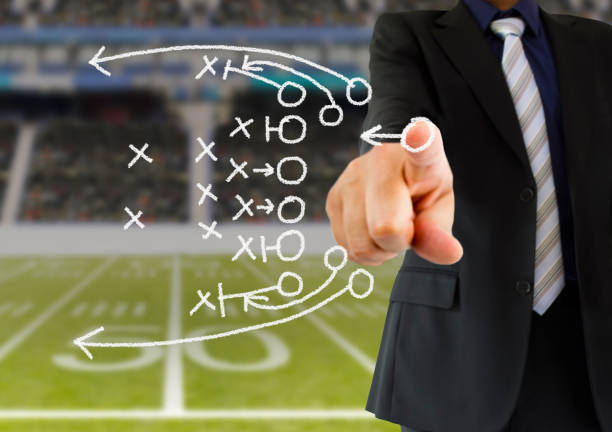 coach drawing a tactics hand of a american football coach drawing a tactics of  football game  with white chalk on blackboard at arena stadium. All screen content is designed by us and not copyrighted by others and created with digitizing tablet and image editor advanced tactical fighter stock pictures, royalty-free photos & images
