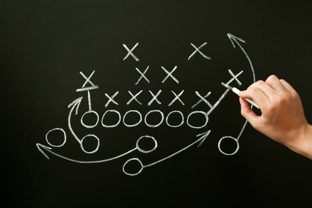 Coach Drawing American Football Playbook Tactics Coach drawing american football or rugby game playbook, strategy and tactics with chalk on blackboard. american football sport stock pictures, royalty-free photos & images