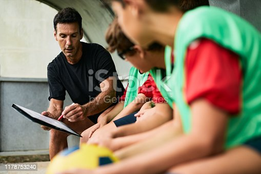 Lifestyle children training and playing soccer. Coach explaining the game plan and strategy on a clipboard.