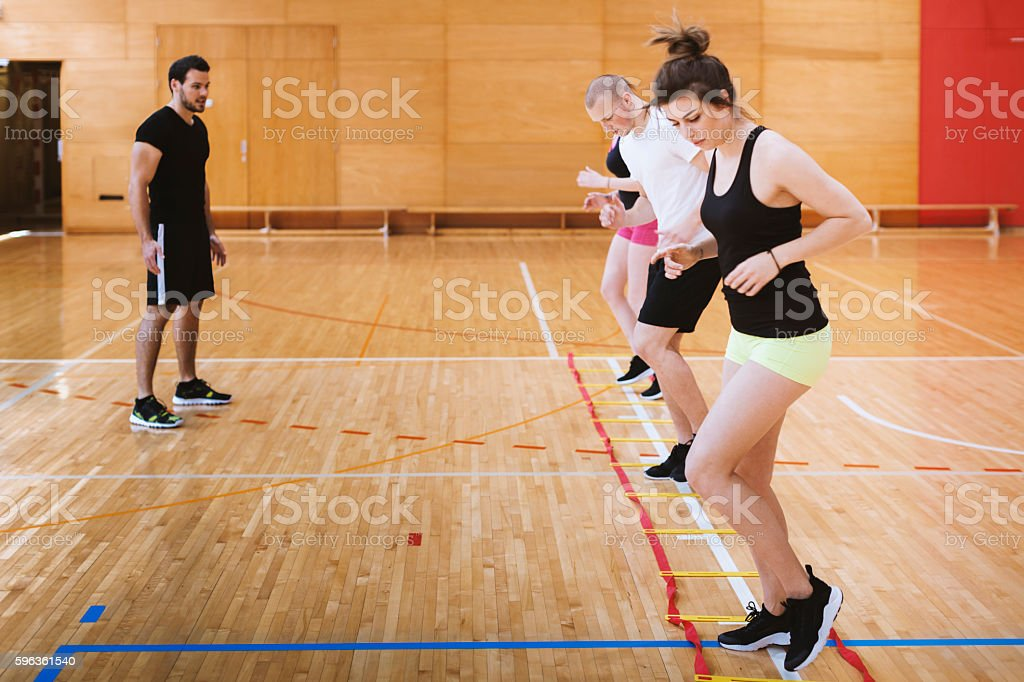 Coach Following Warming Exercises of Young Athletes in Gym royalty-free stock photo