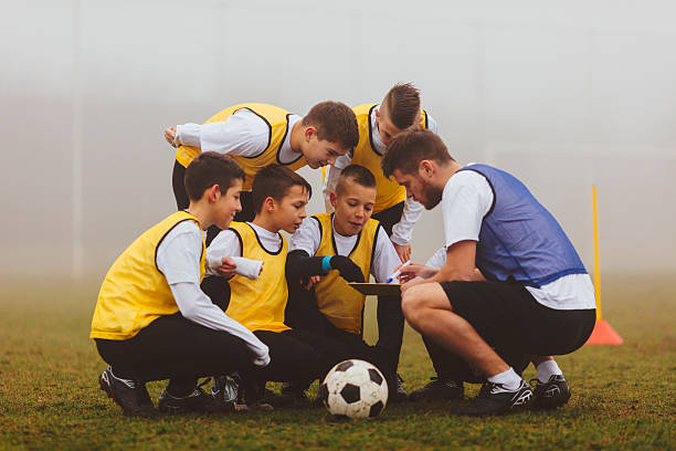coach giving instruction to his kids soccer team. - coach stock photos and pictures