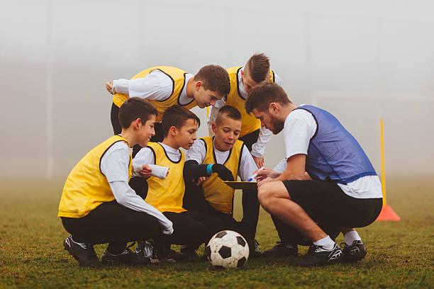 treinador de dar instruções aos seus filhos time de futebol. - equipa de futebol - fotografias e filmes do acervo