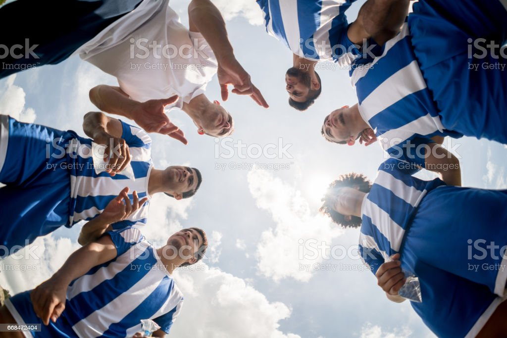 Coach giving instructions to a group of football players stock photo