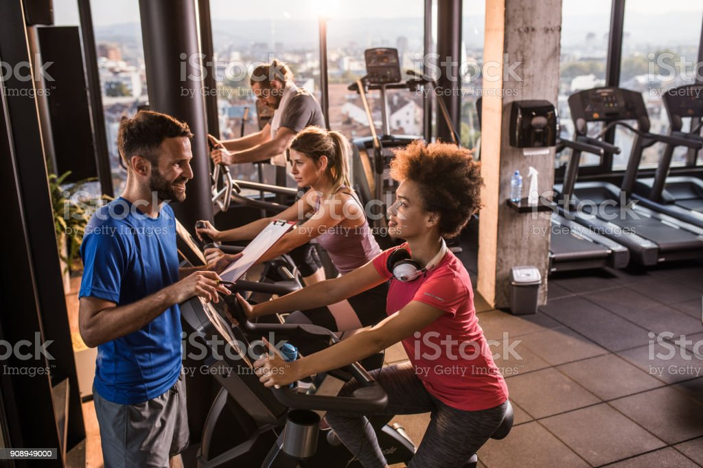Coach Giving Instructions To Athletic People On Spinning Class In A