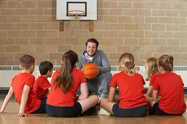 coach giving team talk to elementary school basketball team - middle school teacher stock pictures, royalty-free photos & images