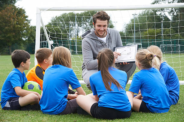 Coach Giving Team Talk To Elementary School Soccer Team stock photo