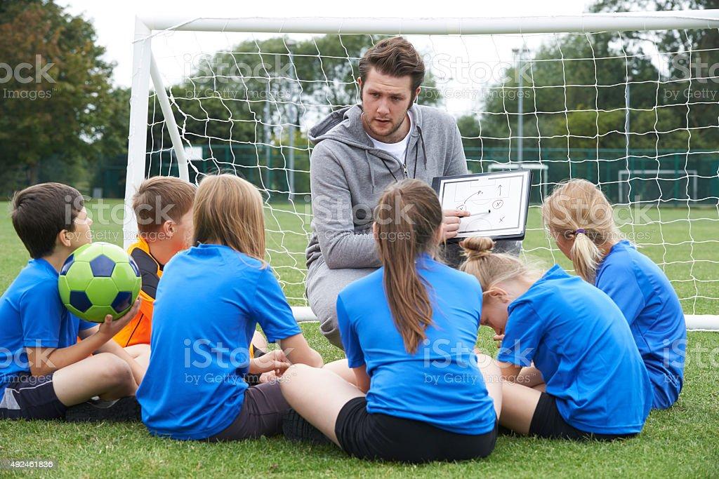 Coach Giving Team Talk To Elementary School Soccer Team stock photo
