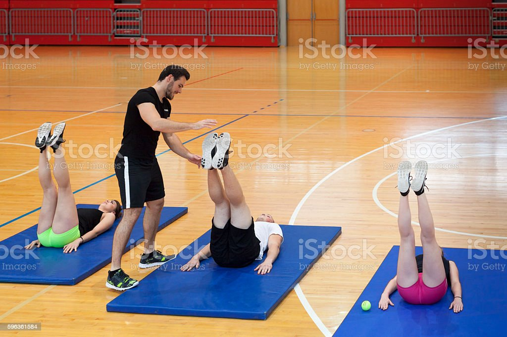 Coach Help Group of Young Athletes Exercises Correctly Indoor Gym royalty-free stock photo
