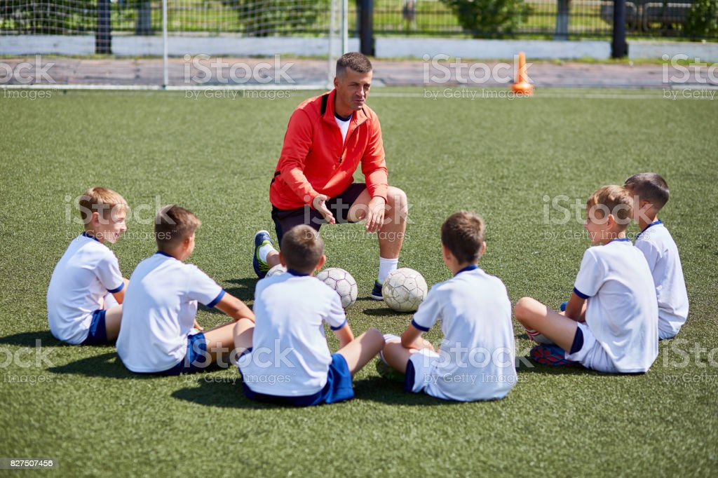 Coach Instructing Junior Football Team in Practice stock photo