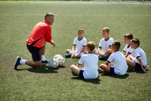 coach instructing junior football team - coach stock photos and pictures
