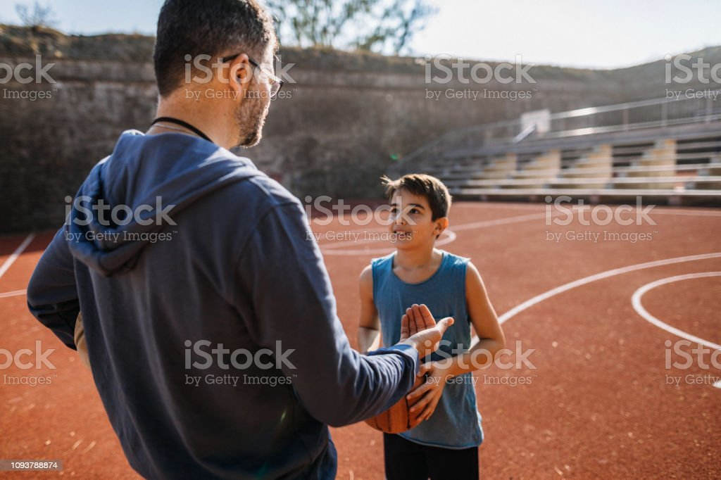 Photo of coach interacting with basketball player