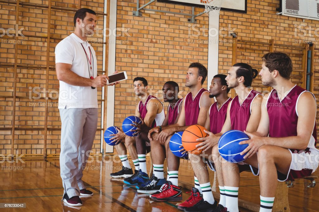 Coach interacting with basketball players stock photo