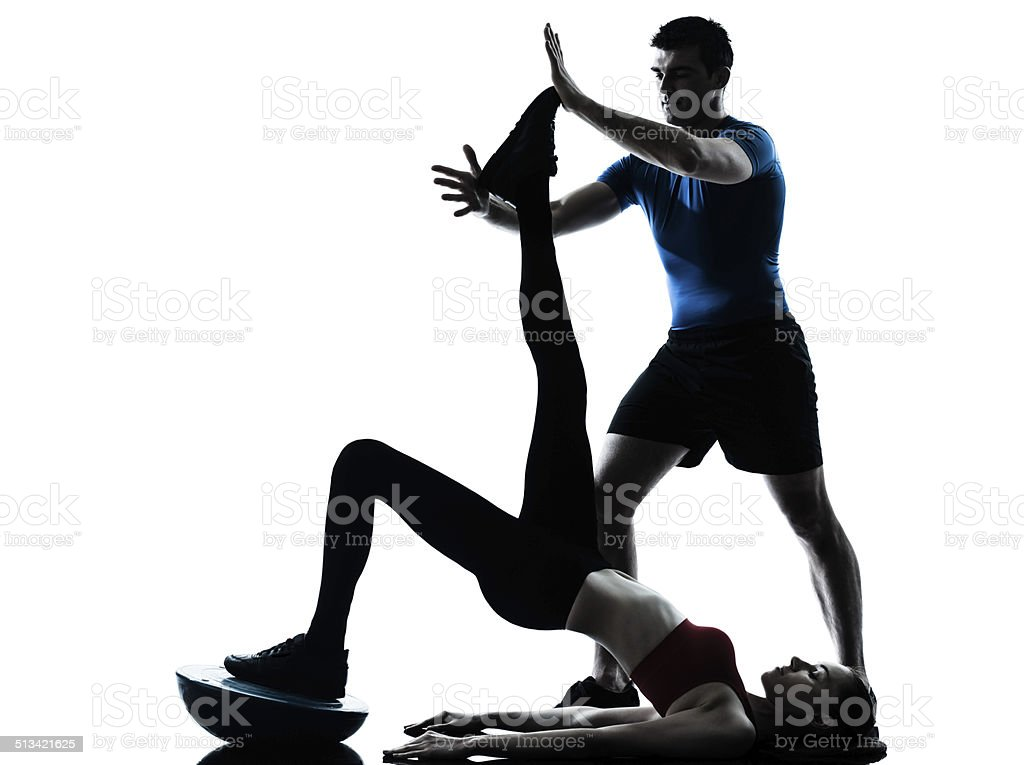 coach man woman exercising abdominals with bosu silhouette stock photo