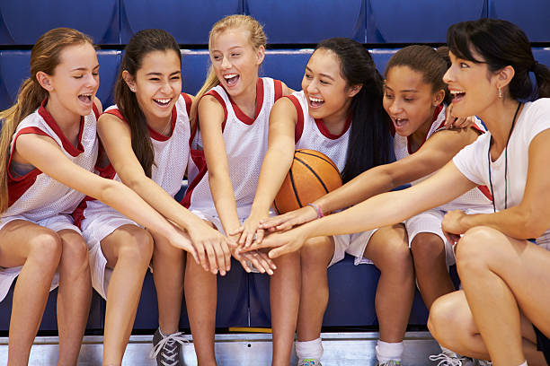 coach of female high school basketball team gives team talk - high school sports stock photos and pictures