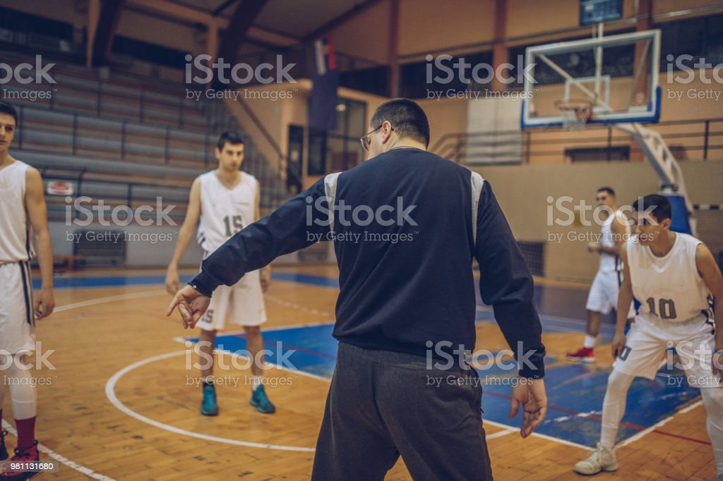 Basketball coach watching his players on training, rear view.