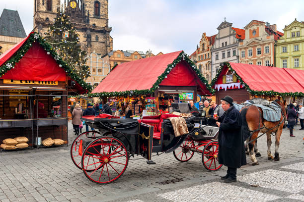 Coach on Old Town Square of Prague during Christmas market. Prague: Carriage and wooden stalls on Old Town Square during traditional annual Christmas market taking place in december in Prague. tyn church stock pictures, royalty-free photos & images