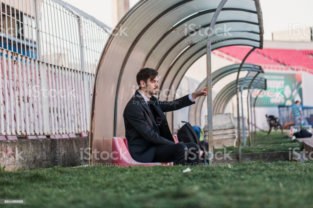 Coach sitting on bench stock photo