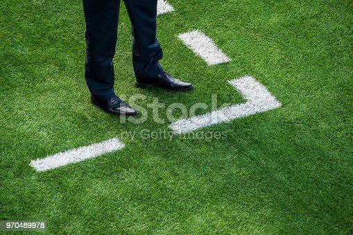 Coach standing next to chalk line on soccer field