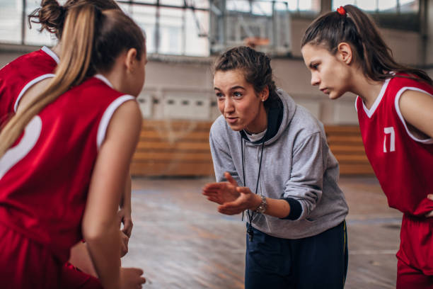 Coach standing with basketball team Female coach standing with basketball team on basketball court high school sports stock pictures, royalty-free photos & images
