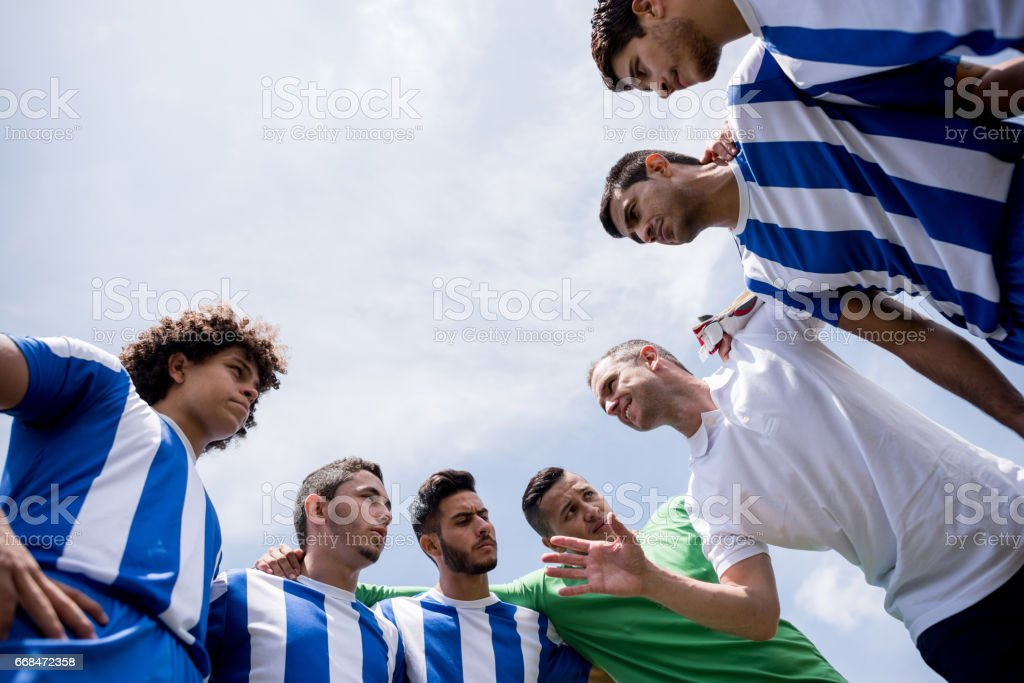 Coach talking to a group of football players stock photo